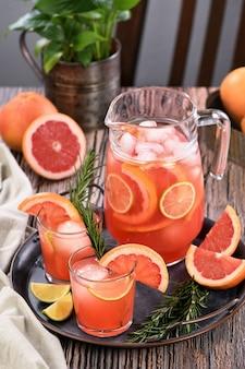Coquetel de toranja fresca. coquetel de verão fresco com grapefruit, limão, raminho de alecrim e cubos de gelo.