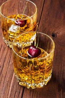 Coquetel de uísque com cereja em dois copos em um fundo de madeira