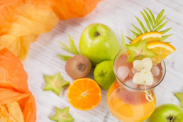 Coquetel de verão com diversas frutas tropicais ao redor