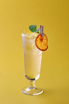 Coquetel de verão fresco com limão, hortelã e gelo em um fundo amarelo.