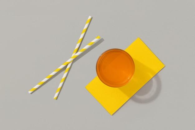 Coquetel de verão laranja sobre superfície cinza vista de cima plana lay,