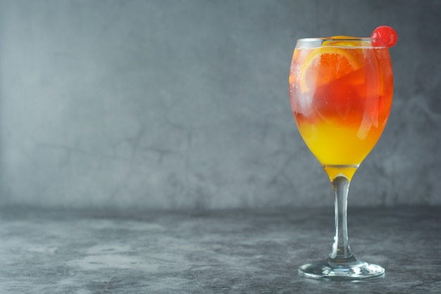 Coquetel de verão. suco de laranja com hortelã, syrop, fatias de frutas e cereja com gelo.