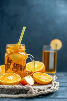 Coquetel de vista frontal corta laranjas e maçãs na placa de madeira no fundo escuro isolado