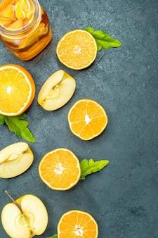 Coquetel de vista superior corta laranjas e maçãs em fundo escuro isolado
