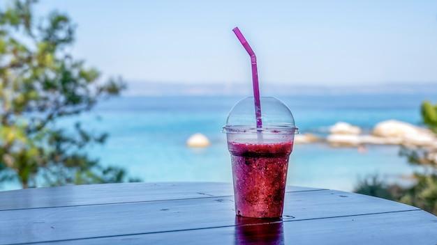 Coquetel em um copo de plástico transparente com canudo e vista da costa do mar egeu, grécia