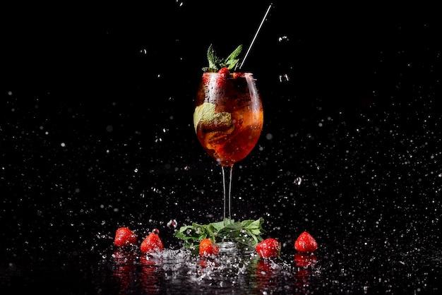 Coquetel em um fundo preto com morangos e hortelã em spray de água. foto de alta qualidade