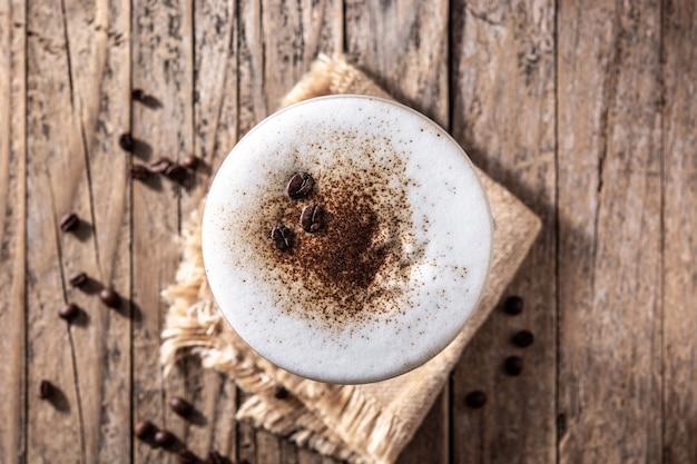 Coquetel expresso martini em copo sobre mesa de madeira