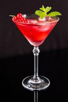 Coquetel frio com groselha na taça de martini no fundo preto. localização vertical.