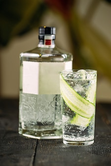 Coquetel gin tônico fresco com pepino em um copo na superfície borrada