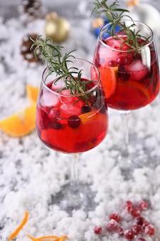 Coquetel margarita com cranberries, laranja e alecrim. um coquetel perfeito para uma festa de natal