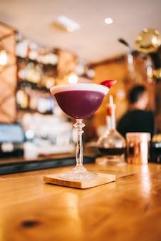 Coquetel marrom requintado em um copo especial em um balcão de madeira contra o fundo de um bar
