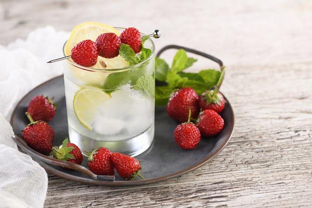 Coquetel mojito orgânico refrescante com rum branco de limão combinado com morango fresco e hortelã