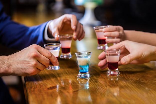Coquetel na boate. grupo de amigos copos de dose de tequila no bar.