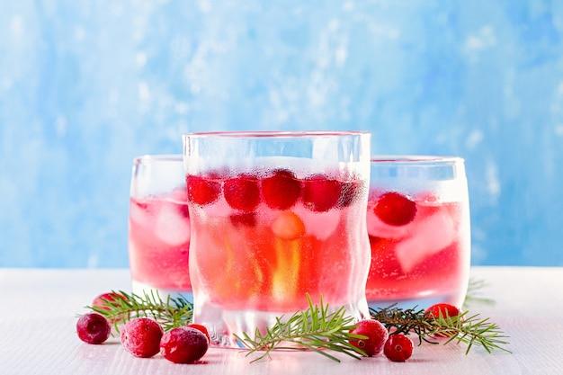 Coquetel não alcoólico de inverno com cranberry e gelo no fundo de madeira, vista de cima