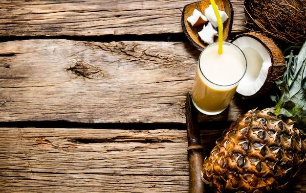 Coquetel pina colada. coquetel fresco com coco, rum e abacaxi em uma mesa de madeira. espaço livre para texto.