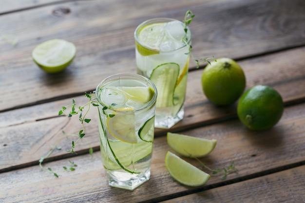Coquetel refrescante caseiro com gim, vodka ou tequila, pepino, limão, cubos de gelo e tomilho em uma mesa de madeira