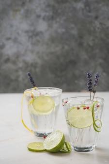 Coquetel refrescante de gin e tônica servido com limão, ervas, especiarias e gelo sobre a mesa de mármore. foco seletivo