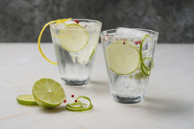 Coquetel refrescante de gin e tônica servido com limão, especiarias e gelo sobre a mesa de mármore. foco seletivo