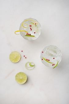 Coquetel refrescante de gin e tônica servido com limão, especiarias e gelo sobre a mesa de mármore. vista do topo