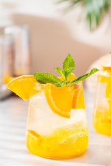 Coquetel refrescante de laranja com gás e sombras