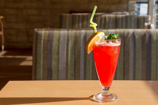 Coquetel refrescante vermelho decorado com hortelã e limão