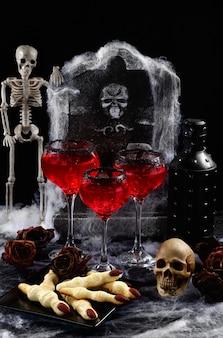 Coquetel sangrento com gelo na mesa com um lanche de biscoitos de bruxa em homenagem ao halloween. festa ideia bebidas
