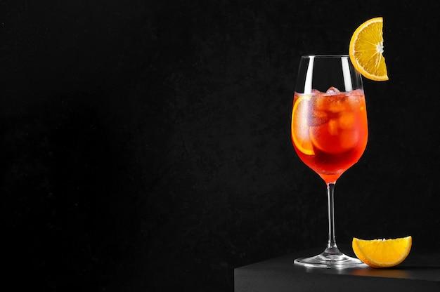 Coquetel spritz em taça de vinho com gelo e uma fatia de laranja em fundo escuro