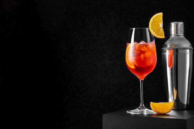 Coquetel spritz em taça de vinho com shaker e fatia de laranja em fundo escuro