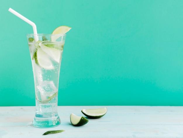 Coquetel transparente com limão, hortelã e gelo no estúdio