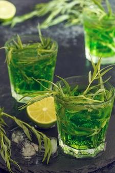 Coquetel verde com limão, refrigerante e gelo picado com folhas de estragão