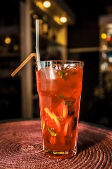 Coquetel vermelho em um copo alto com gelo fino e limão, limão, folhas de hortelã, amora, groselha, cranberries e palha amarela. beba em um copo para o menu do restaurante, bar, café.