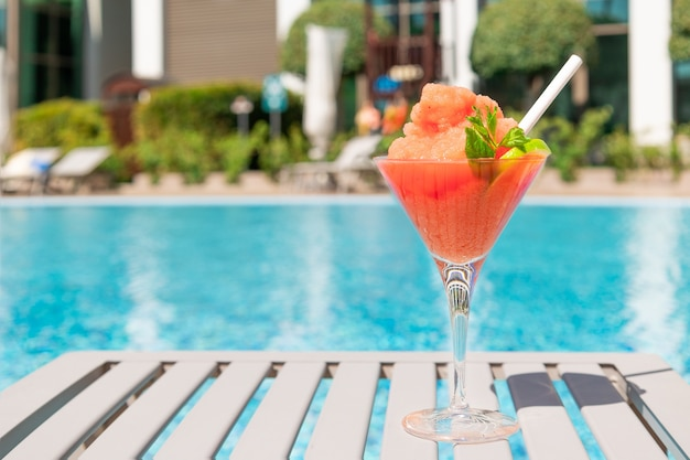 Coquetel vermelho fresco com gelo em copo na piscina suco tropical em férias luxuosas