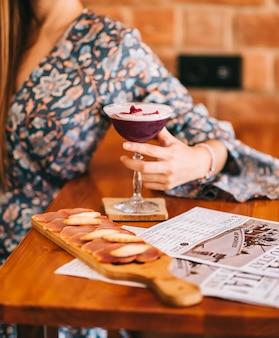 Coquetel vermelho-vinho requintado em um copo especial em um balcão de madeira contra o fundo de um balcão de bar