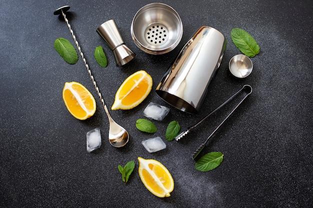 Coqueteleira e ferramentas de bar. ingredientes para um coquetel alcoólico frio. mojito cocktail. limão, hortelã, gelo, rum. vista superior, horizontal, fundo preto, copie o espaço