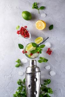 Coqueteleira, limão, limão, folhas de hortelã, groselha e gelo para preparar um coquetel de verão