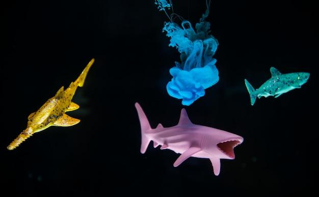 Cor acrílica se dissolvendo na água com tubarões de brinquedo