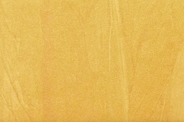 Cor amarela clara do fundo da arte abstrata. pintura dourada sobre tela. fragmento de arte. pano de fundo de textura ocre. papel de parede decorativo.