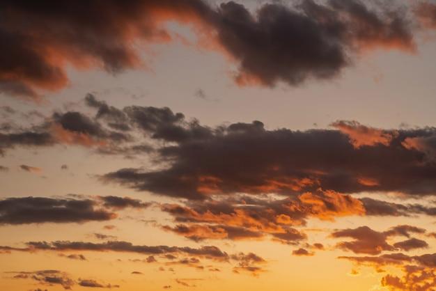 Cor amarelo-laranja púrpura do céu nublado na hora do pôr do sol