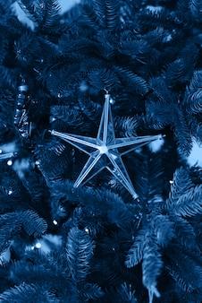 Cor azul clássica do ano 2020. estrela de brinquedo de natal de vidro na árvore de natal