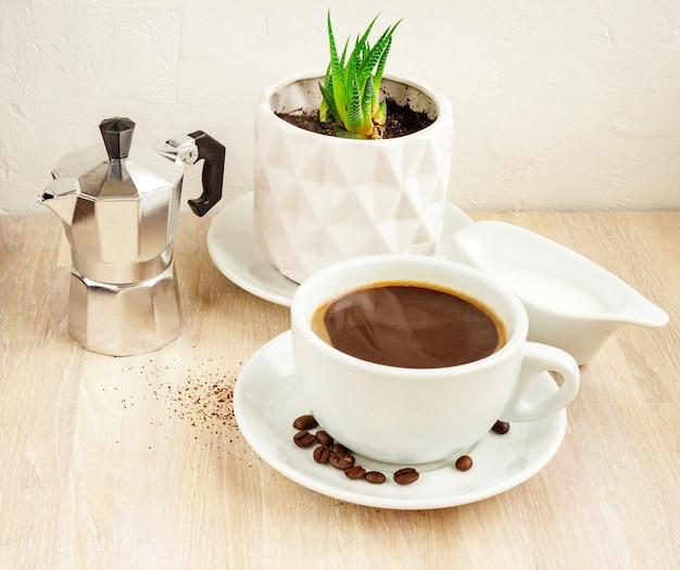 Cor branca xícara de café preto com pires e feijão, cafeteira de alumínio, recipiente para leite com leite, planta suculenta verde em pote branco na mesa de madeira bege. foco seletivo. copie o espaço