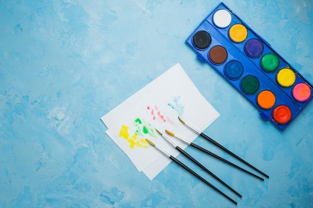 Cor de água manchada em papel branco com pincel e paleta de cores sobre a superfície azul