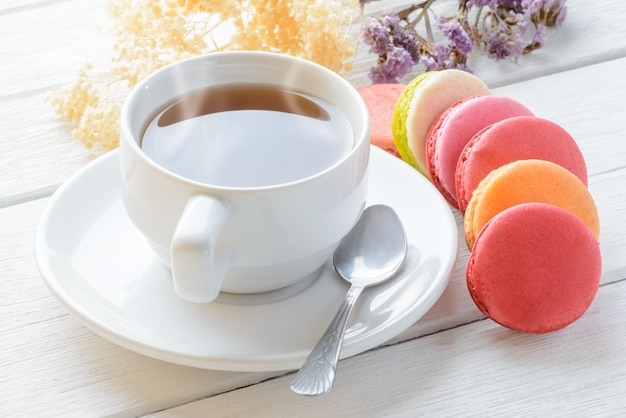 Cor de diferentes tipos de macaroons com xícara de chá quente em madeira branca
