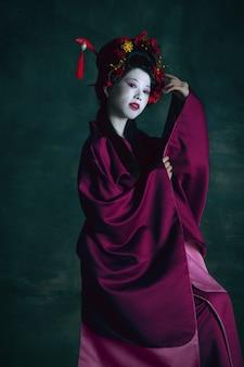 Cor de vinho. jovem mulher japonesa como gueixa isolada em fundo verde escuro. estilo retro, comparação do conceito de eras. bela modelo feminina como personagem histórica brilhante, antiquada.