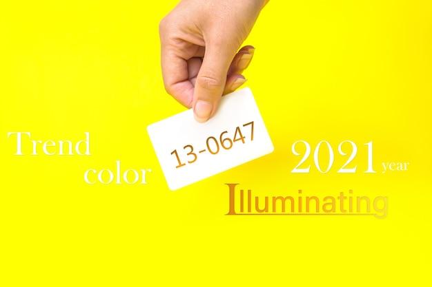 Cor do ano de 2021. mão segurando um cartão de visita com o texto 13-0647, iluminando em backg amarelo
