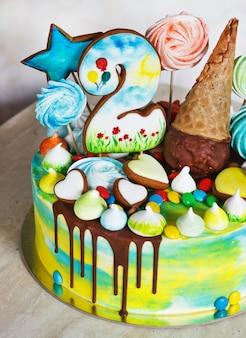 Cor do arco-íris do bolo moderno infantil em uma superfície branca com merengue de madeira