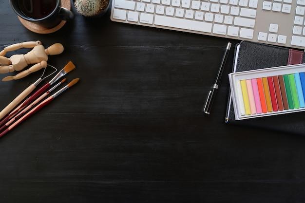 Cor do espaço de trabalho do artista com acessórios criativos na tabela de madeira escura. espaço de trabalho e espaço de cópia.