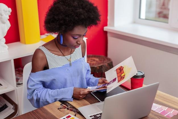 Cor para sofá. designer de interiores vestindo roupas brilhantes e trabalhando arduamente para escolher a cor do sofá na sala de estar