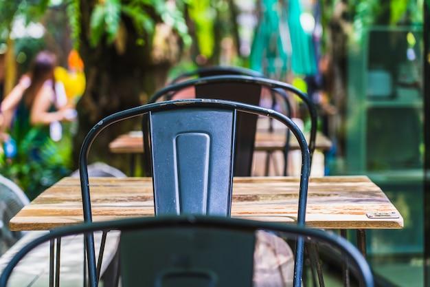 Cor preta de cadeiras de metal e mesa de madeira no jardim