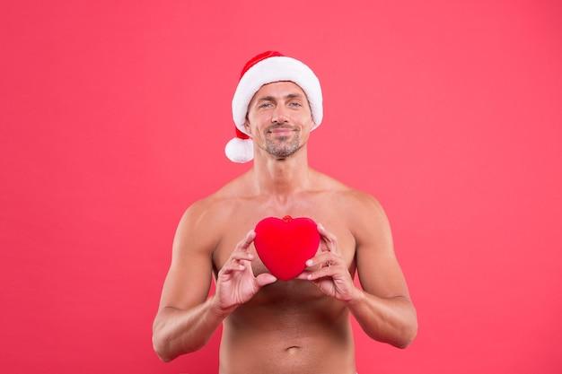Coração adorável. cuidados com a pele. homem bonito comemorar fundo vermelho de férias de inverno. cara usa chapéu de inverno. feliz natal e feliz ano novo. torso nu de homem maduro. corpo atraente. inverno.