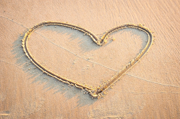 Coração afiado é desenhar à mão na areia